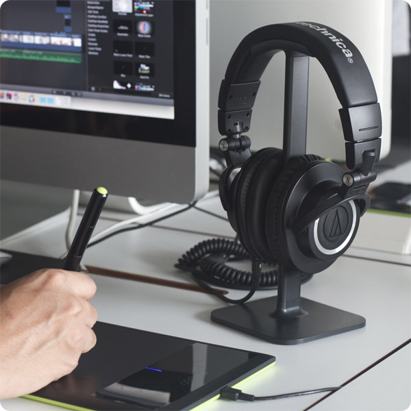 Posto: Holding headphones by iMac (Black)
