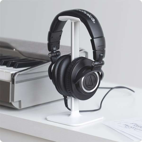 Posto: Holding studio headphones by keyboard (White)
