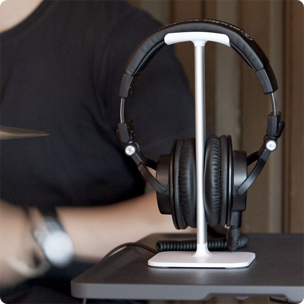 Posto: Holding studio headphones by drumset (White)